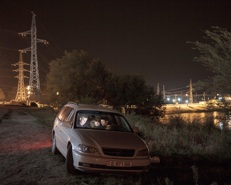 Igor, Ira und Anatoli haben sich an den Stadtrand von Dubossary zurückgezogen, um im Auto von Anatolis Eltern Filme zuschauen. Das Wasserkraftwerk im Hintergrund besitzt hohe strategische Bedeutung für Transnistrien, die heutige Grenzlinie verläuft nur knapp dahinter.