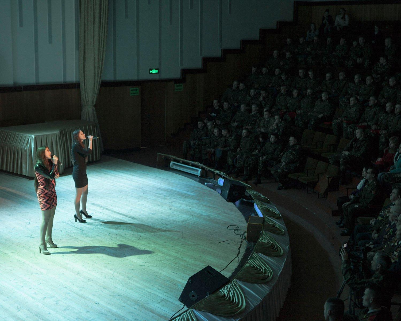 """Am """"Tag des Vaterlandverteidigers"""" werden die Angehörigen der Armee gefeiert. Zwei junge Sängerinnen geben ein Konzert zu Ehren der Veteranen, die in der ersten Reihe platz genommen haben."""